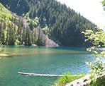 Looking across Lindeman Lake towards a rock slide on the other side