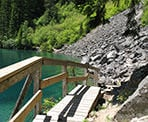 A wooden walkway along the trail that passes Lindeman Lake