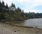 A rocky beach with houses along the cliff near Whytecliff Park in West Vancouver